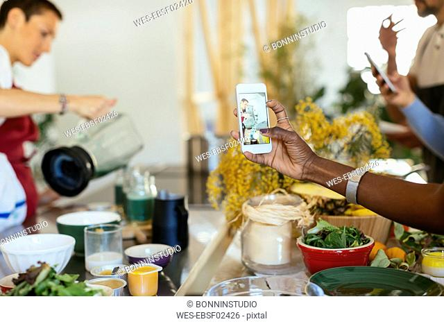 Close-up of woman taking smartphone picture of instructor working in a cooking workshop