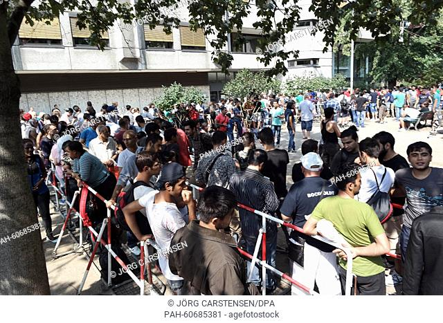 Refugees queue up in front of the 'Landesamt für Gesundheit und Soziales Berlin' (LaGeSo, lit. State Office for Health and Social Affairs) during hot summer...