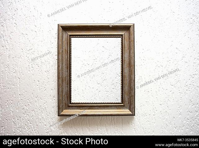 One empty wooden frame on a white wall background texture, retro modern design space for text