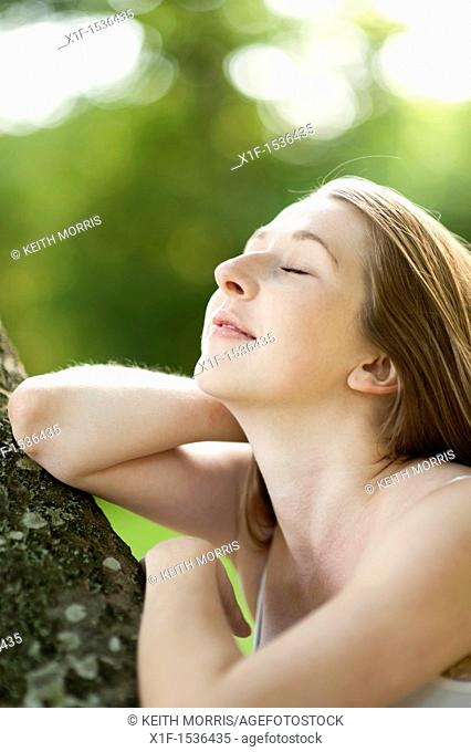 a young caucasian woman eyes closed, outdoors in a woodland glade, uk