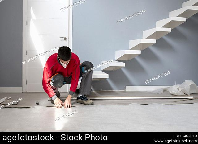 repairman laying flooring in apartment using a mask due to the corona virus pandemic
