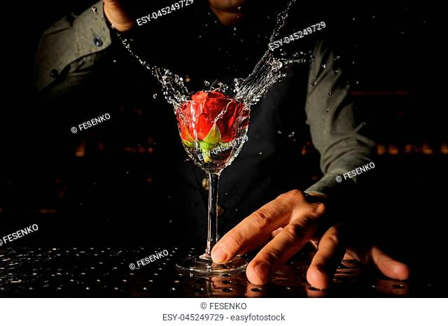 Barman putting a beautiful red rose into the cocktail glass on the steel bar counter