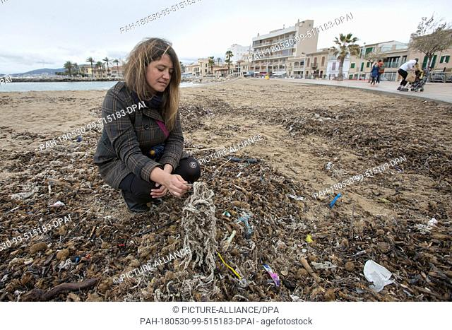 20 March 2018, Spain, Mallorca: Aina Barcelò from the environment organisation 'Ondine Baleares' examining rubbish on the beach in the Palma bay which has got...