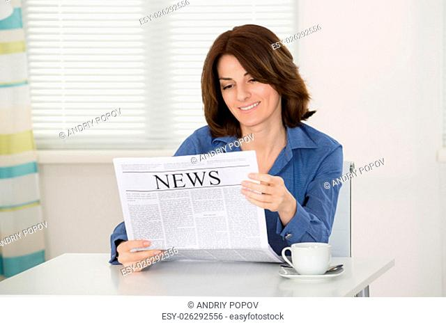 Happy Young Woman Reading Newspaper At Home