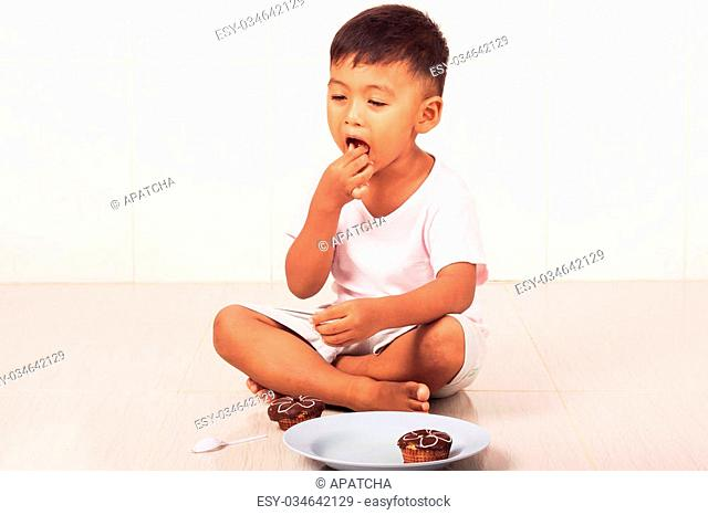 little boy eating chocolate cake in the room
