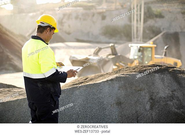 Worker standing at quarry, using clipboard