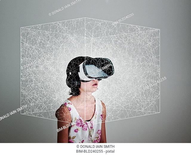 Mixed Race girl wearing virtual reality goggles in floating box