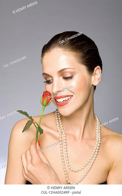 Female beauty model smelling rose