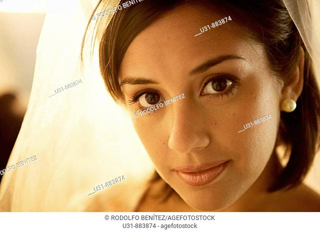 Bride in her 20s looks at the camera during make up