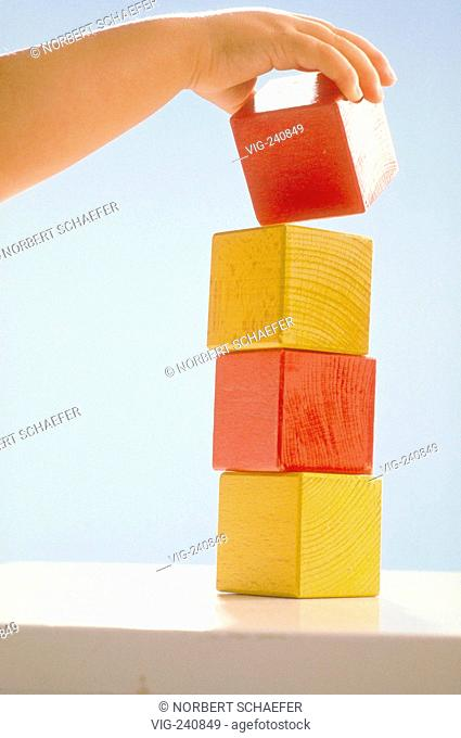 close-up, hand of baby putting red and yellow playing blocks on top of each other  - GERMANY, 27/04/2003