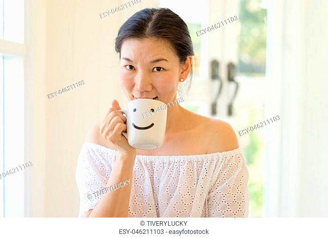Woman hands holding a white coffee mug