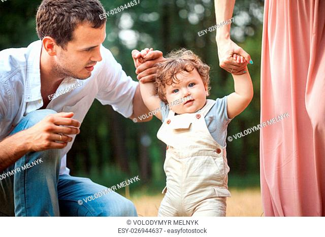 Young beautiful father, mother and little toddler son against green trees. Happy family with her baby boy on a summer sunny day