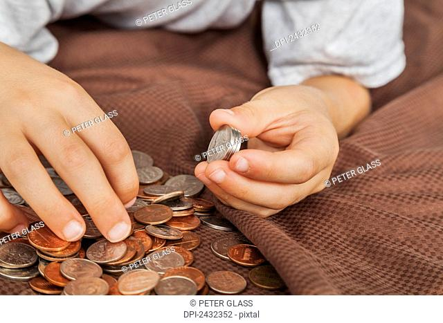 Young boy's hands counting American money; Connecticut, United States of America
