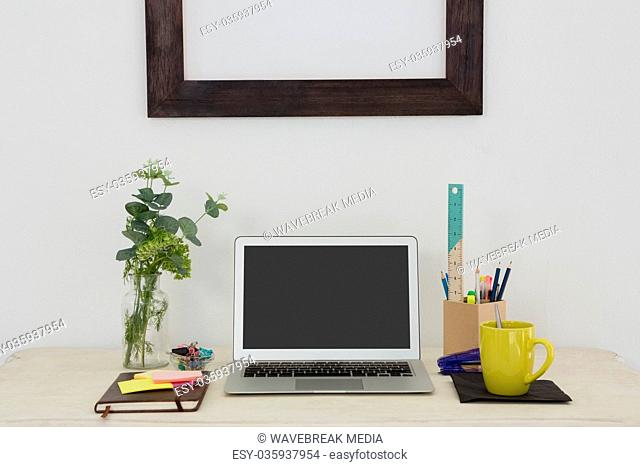 Laptop and various office accessories on table