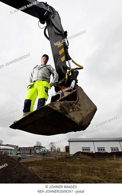 Worker standing on scoop