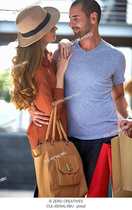 Couple, face to face, holding shopping bags