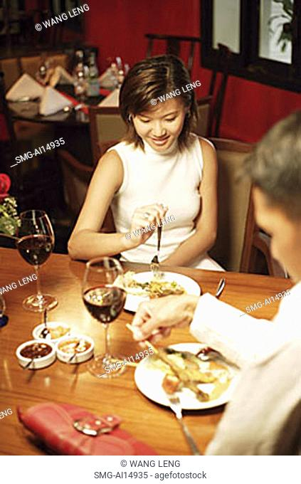 Couple at restaurant, eating, over the shoulder view