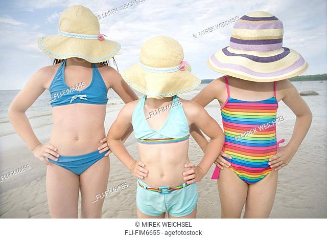 Three girls covering their faces with hats, Grand Beach, Manitoba