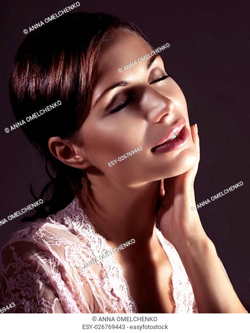 Portrait of a gentle nice female with closed eyes enjoying using cosmetics, isolated on black background, natural beauty
