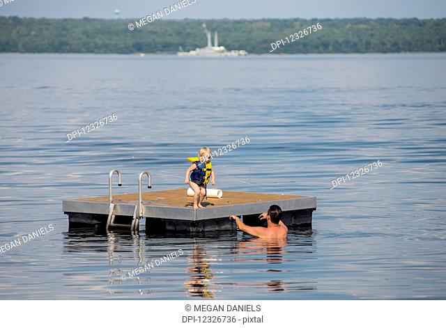 A young Caucasian girl prepares to jump off a floating dock into her dad's arms in Seneca Lake in upstate New York, the naval barge, no longer in service