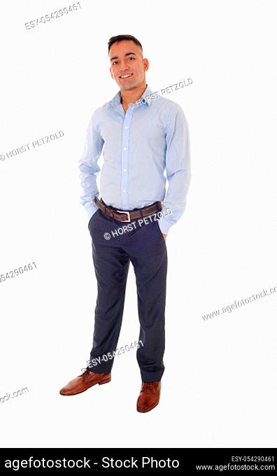 A handsome young east Indian man standing in a blue shirt with his.hands in his pocket, smiling, isolated for white background