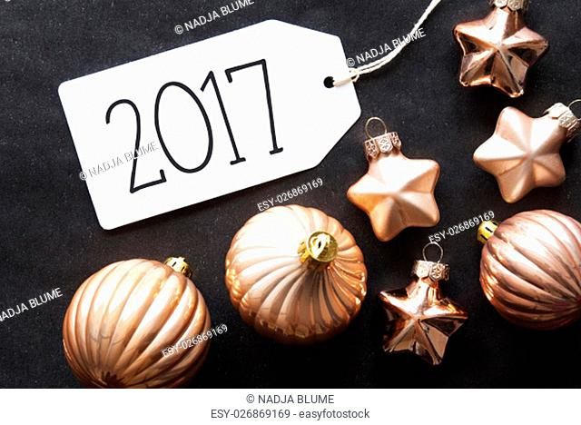 Label With Text 2017 For Happy New Year. Bronze Christmas Tree Balls On Black Paper Background. Christmas Decoration Or Texture. Flat Lay View