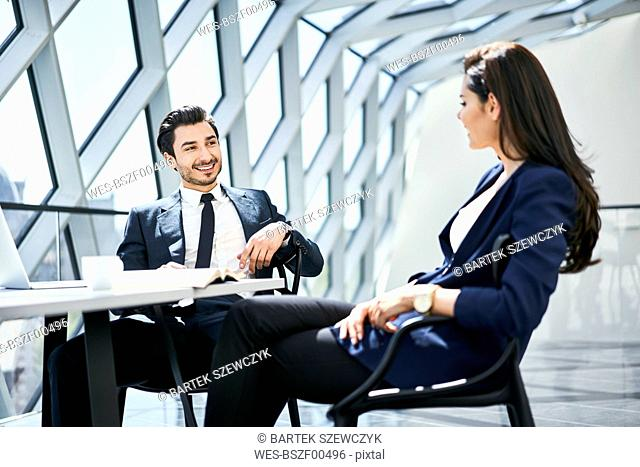 Businesswoman and businessman talking at desk in modern office