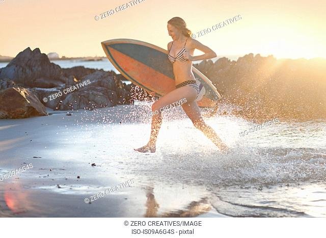 Young woman with surfboard running on beach