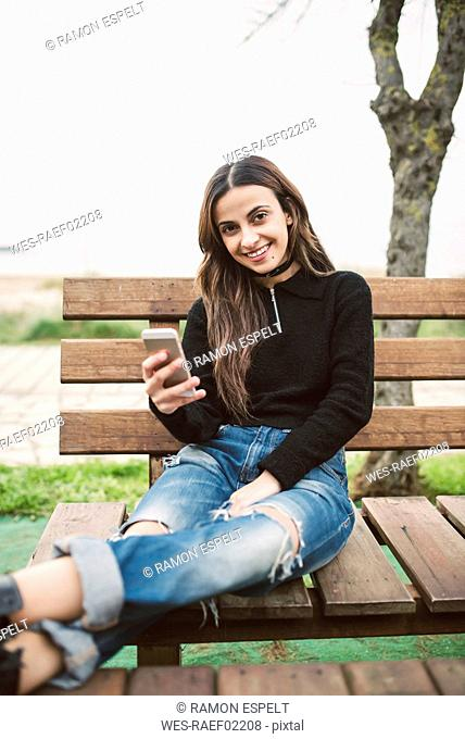 Portrait of smiling young woman with cell phone sitting on bench outdoors