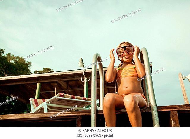 Girl wearing snorkel mask sitting at poolside