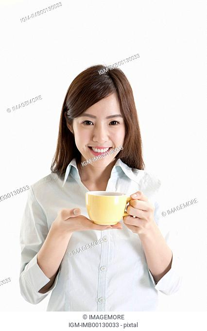 Young woman holding a cup of coffee and smiling at the camera