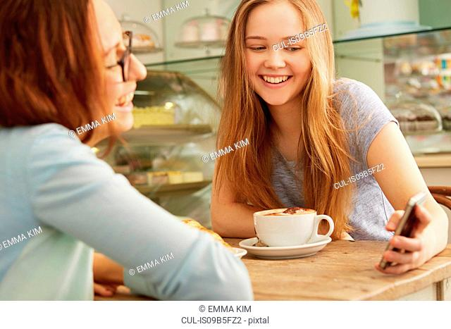 Friends in cafe looking at smartphone smiling