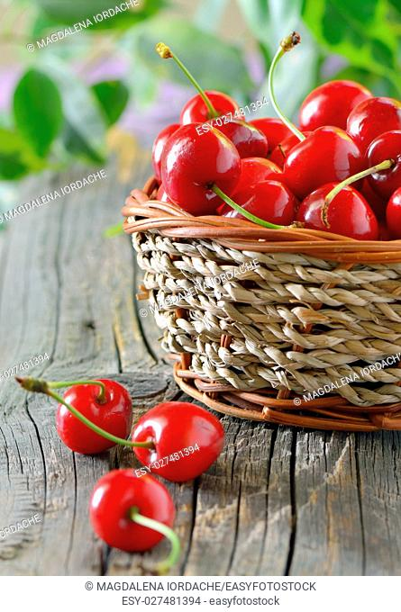 ripe cherries in a basket on wooden table