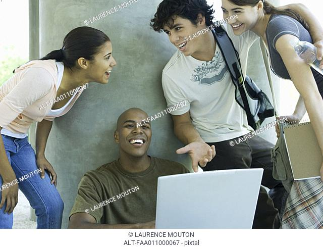 College students looking at laptop and laughing