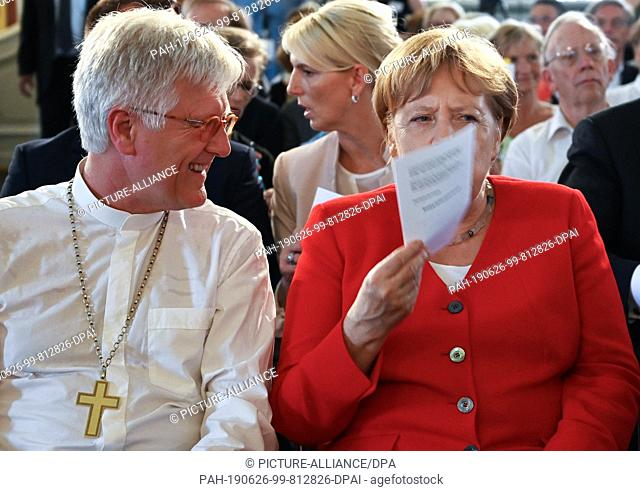 26 June 2019, Berlin: Federal Chancellor Angela Merkel (CDU) sits next to Heinrich Bedford-Strohm, Chairman of the Council of the Evangelical Church in Germany