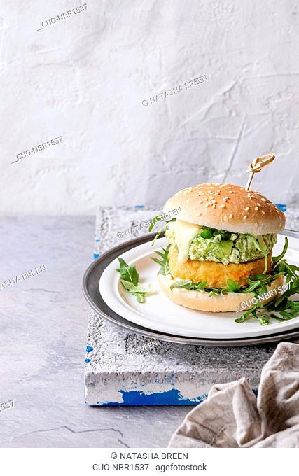 Vegetarian hamburger with onion and cheese cutlets, avocado salad, arugula and yogurt sauce in white plate over gray stone texture background