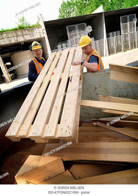 Workers hauling plywood on site