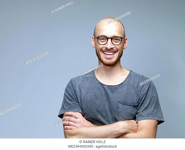 Portrait of smiling man with crossed arms in front of grey background