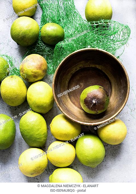 Overhead view of lemons in bowl and net packaging