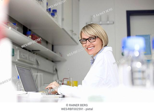 Smiling scientist using laptop in laboratory