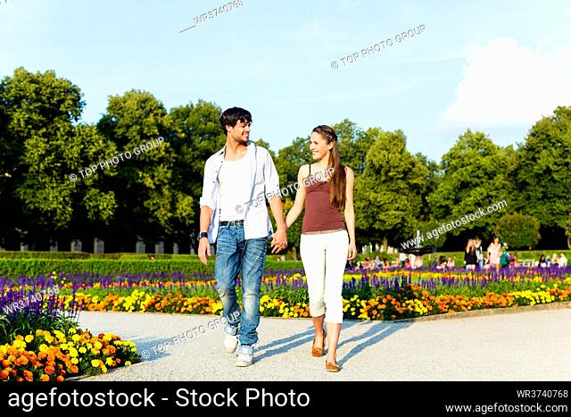 Man and woman or young couple making a trip as tourists in park waling hand in hand