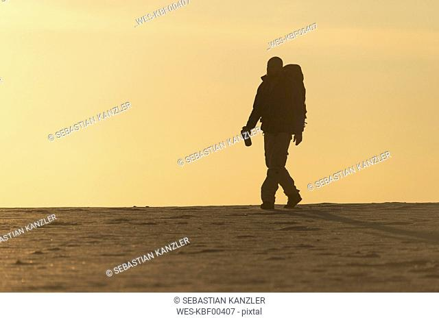 Man with backpack at the beach in the evening light