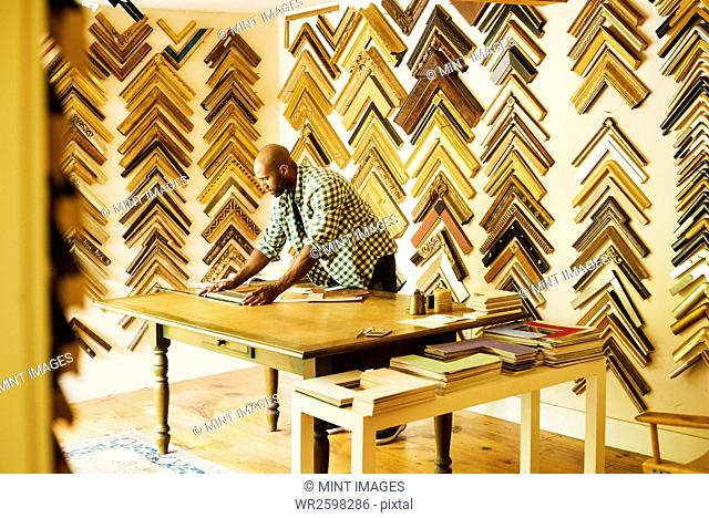 Man working at a picture framers, a large selection of frames on the walls