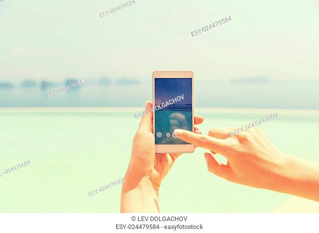 technology, travel, tourism, communication and people concept - close up of male hand holding smartphone on summer beach