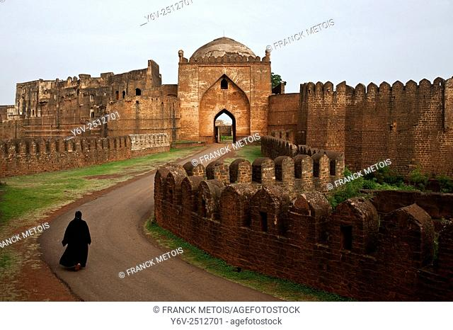 A traditionally dressed muslim woman is walking inside the fort at Bidar in Karnataka, India. She is on her daily morning walk
