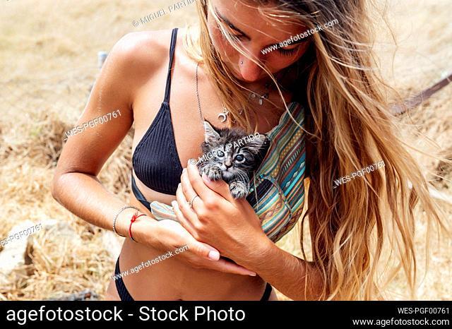 Hipster woman holding kitten in waist pack