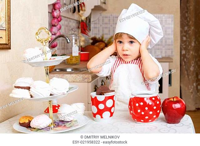 Little girl in apron in the kitchen