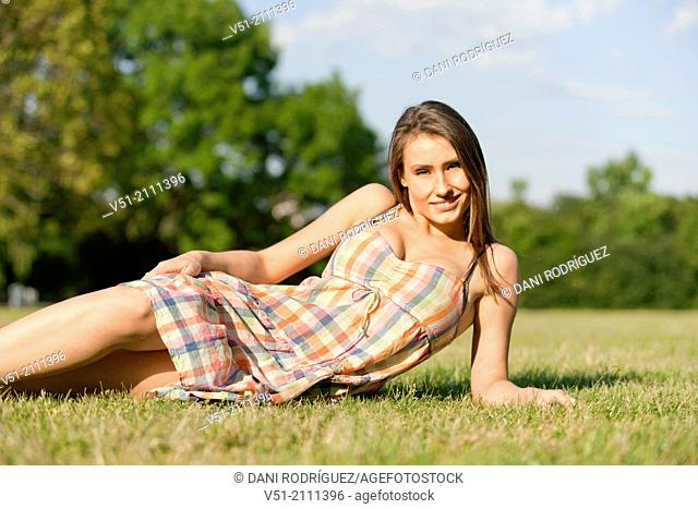 Sexy brunette woman in park smiling at camera