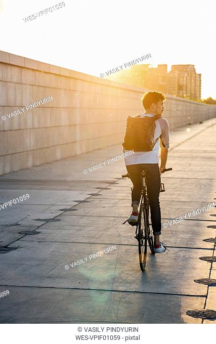 Young man with backpack riding bike on promenade at sunset