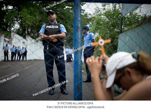 """29 May 2018, Germany, Managua: A woman holding a cross in front of """"""""El Chipote"""""""" prison hopes to receive information about incarcerated relatives"""